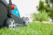 Lawn mower on a green meadow.