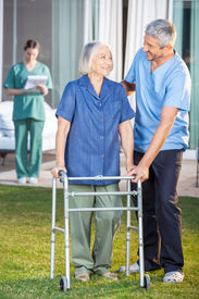 stock photo of zimmer frame  - Male caretaker helping senior woman to use walking frame with female nurse in background at nursing home lawn - JPG
