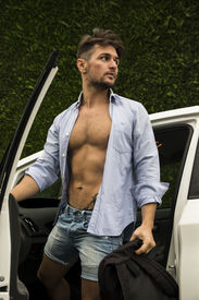 stock photo of muscle-car  - Gorgeous Young Man in Beach Attire Getting Out his Car Showing Sexy Body Abs - JPG