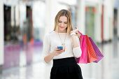 picture of shopping center  - Happy teenage girl holding bags with purchases smiling while looking at phone in shopping center - JPG
