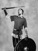 stock photo of knights  - Victorious medieval knight armor with a sword and shield black and white image - JPG