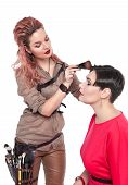 picture of makeup artist  - Professional makeup artist making makeup to a model isolated on white background