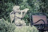 stock photo of cupid  - little cupid angel with spreaded wings in an irish garden - JPG