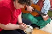 image of disability  - a mentally disabled woman playing a tamborin - JPG