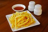 stock photo of potato chips  - French fries or potato chips with ketchup and salt and pepper - JPG