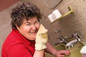 stock photo of independent woman  - a happy mentally disabled woman with a washcloth - JPG