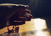 picture of rosary  - Hand holding rosary towards the light in prayer - JPG