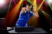 picture of mixer  - caucasian male dj playing mp3 music with computer and mixer - JPG