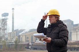 image of polution  - Sugar refinery worker standing outdoors wearing yellow hardhat and holding clipboard in his hands - JPG