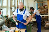 image of dungarees  - two worker in blue dungarees in a carpenter