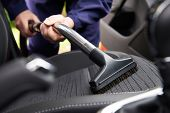 Man Hoovering Seat Of Car During Car Cleaning poster