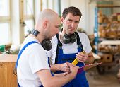 pic of dungarees  - two worker in blue dungarees in a carpenter - JPG