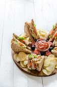 image of potato chips  - Large group of clup sandwiches with potato chips and ketchupselective focus and blank space - JPG