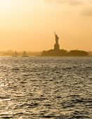 stock photo of hazy  - Statue of Liberty and Liberty Island across New York Harbor in hazy sunset light - JPG