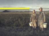 picture of mongolian  - Mongolian couple farmers holding basin and posing in the field - JPG