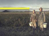 foto of mongolian  - Mongolian couple farmers holding basin and posing in the field - JPG