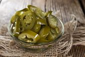 pic of jalapeno  - Heap of sliced Jalapenos on rustic wooden background - JPG