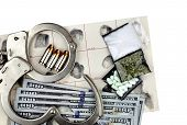 stock photo of handcuffs  - Drug bust arrest with handcuffs cash fingerprint ID and fake sample evidence - JPG