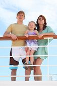 Family With Daughter Standing On Cruise Liner Deck Near Rail, Child Standing On Fence