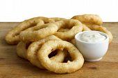 stock photo of dipping  - Heap of deep fried onion or calamari rings with garlic mayonnaise dip on wood board - JPG