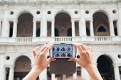 picture of vicenza  - Tourist girl using her smartphone to take a photo of the Basilica Palladiana a landmark of Vicenza - JPG