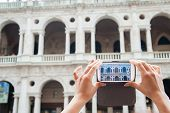 pic of vicenza  - Tourist girl using her smartphone to take a photo of the Basilica Palladiana a landmark of Vicenza - JPG