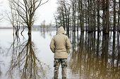 foto of observed  - Man in jacket and military pants standing on shore and observing river - JPG