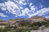 foto of cumulus-clouds  - Aztec sandstone geological rock formations along seasonal wash under blue sky with cumulus clouds during sping in Red Rock national conservation area Nevada - JPG