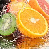 fruta en un chorro de agua aislado sobre un fondo blanco.