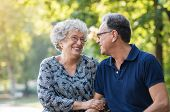 Portrait of a senior couple smiling and looking each other at park. Happy old man and woman sitting  poster