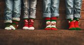 Merry Christmas and Happy Holidays. Group of four kids on wooden background. Childrens feet in sock poster