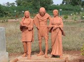 picture of mahatma gandhi  - Shot near a new park near our village was this uniquely colored mahatma supported by 2 women - JPG