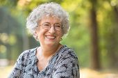 Portrait of smiling elderly woman with eyeglasses at park. Laughing senior woman looking away. Happy poster