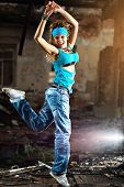 Young woman dancing on industrial background.