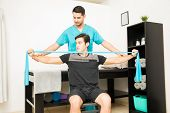 Physical Therapist Helping Male Patient Using Resistance Band To Exercise In Hospital poster