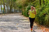Determined Middle-aged Woman Jogging During Cardio Workout For Burning Calories Outdoors In The Park poster