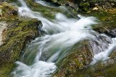 stock photo of gushing  - A Flow of Gushing Water over Rocks - JPG