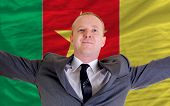 Happy Businessman Because Of Profitable Investment In Cameroon Standing Near Flag