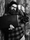 Bearded Man, Long Beard. Brutal Caucasian Serious Unshaven Hipster Holding Laptop With Mag Or Cup In poster