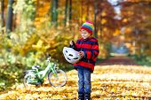 Little Kid Boy In Colorful Warm Clothes In Autumn Forest Park With A Bicycle. Active Child Putting S poster