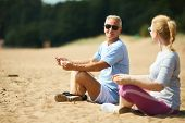 Senior man and his wife in activewear meditating on sand after morning workout poster
