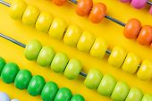 Colorful Wooden Abacus Beads On Vivid Yellow Background, Business Financial Or Accounting Profit And poster