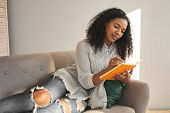 Indoor Shot Of Trendy Looking Young African American Woman Wearing Ripped Jeans Lying On Comfortable poster