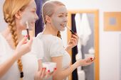 Skincare. Blonde Woman In Bathroom Applying With Brush Gray Clay Mud Mask To Her Face. Young Lady Ta poster