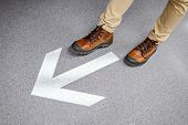 Male Feet With Casual Shoes Stepping Over Light Arrowhead Go Forward Sign On The Floor. Keep Moving  poster
