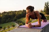 Plank It! Full Length Of Young Beautiful Fit Woman In Sportswear Doing Plank Against Industrial City poster
