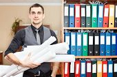 Businessman standing with rolled blueprints in hands
