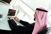 Empresario árabe moderno en la oficina trabajando en portátil