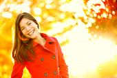 Autumn fashion girl wearing red trench coat in sun flare foliage. Fall woman portrait of happy lovely and beautiful mixed race Asian Caucasian young woman in forest in fall colors.