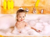 Little girl washing in bubble bath .